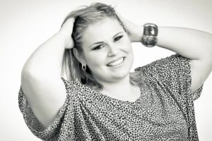Close up of a Blonde Plus size woman, a model. The woman has her hands in the hair. In black and white.